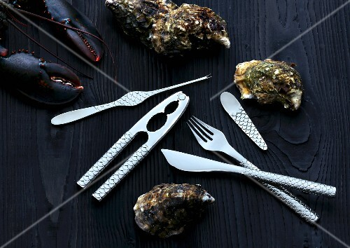 Cutlery for fish and seafood next to oysters and lobster