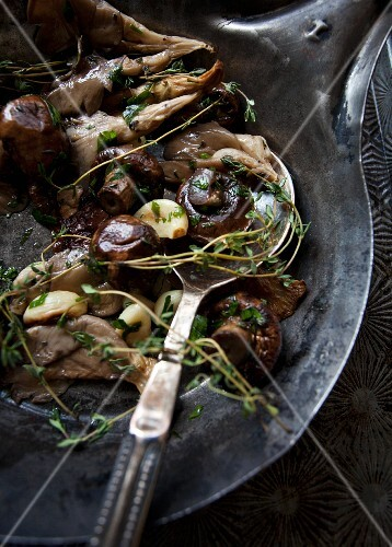Various types of roasted mushrooms with garlic and thyme in an antique pan