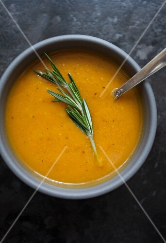Roasted vegetable soup topped with a sprig of rosemary