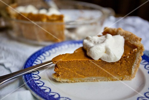 A slice of pumpkin pie with a dollop of cream on the blue and white plate