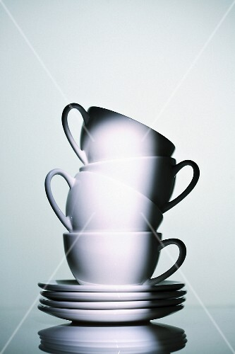 A stack of white cups and saucers