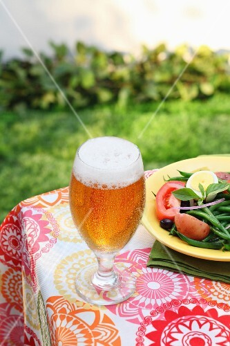 A glass of Pils on a garden table next to a plate of summer salad