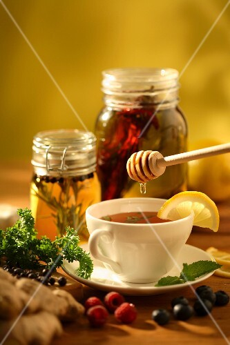 Herb tea being sweetened with honey