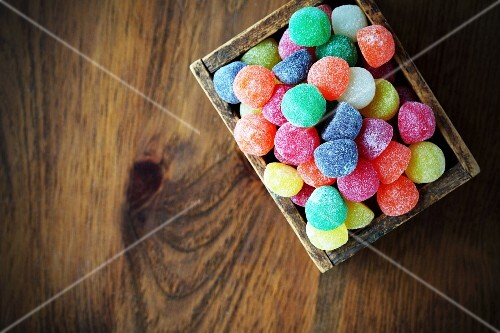 Colourful jelly sweets in a wooden crate (seen from above)