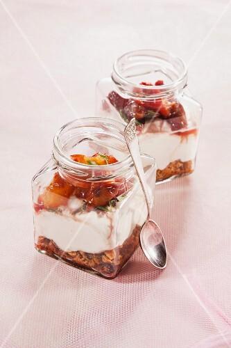 Layered desserts made with muesli, quark and nectarines in jars
