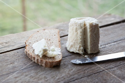 Goat's cheese on a slice of bread on a wooden table