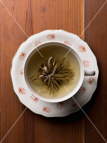 A cup of herb tea with the tea flower on a wooden table