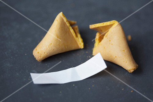 A broken fortune cookie on a table