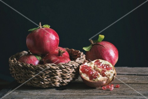 Pomegranates in a basket and next to it on a wooden table