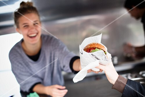 A laughing young woman selling a hamburger