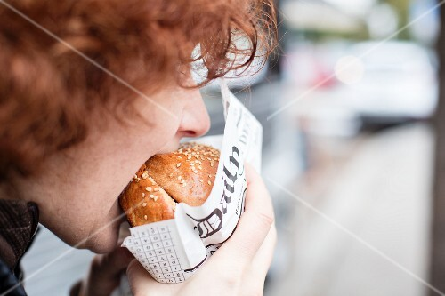 A red-haired teenager biting into a hamburger