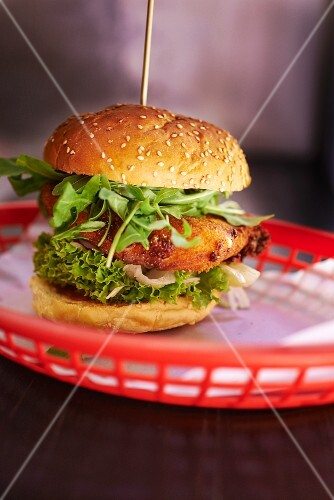 A burger with breaded mozzarella and rocket