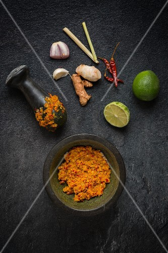 Red curry paste in a mortar with ingredients next to it