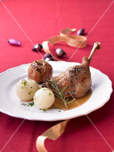 Festive goose leg with potato dumplings and baked apples