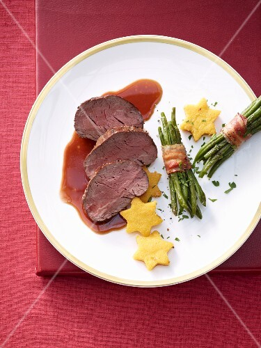 Beef fillet with polenta stars and beans wrapped in bacon