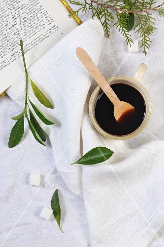 Black coffee and a cop with a wooden spoon with sugar cubes and leaves next to it