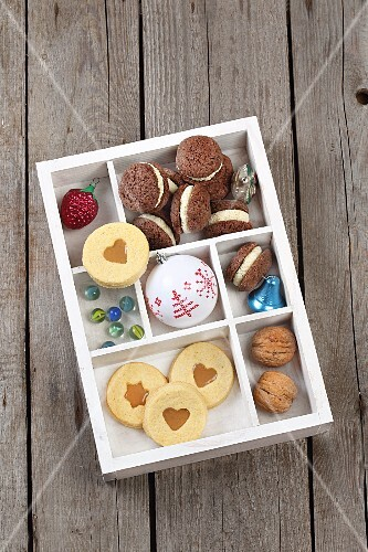 Biscuits, Christmas decorations and nuts in a seedling tray