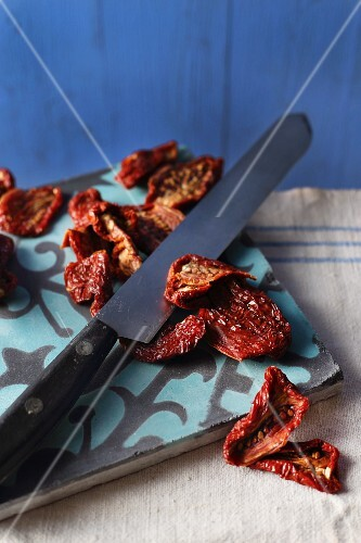 Dried tomatoes on a chopping board with a knife