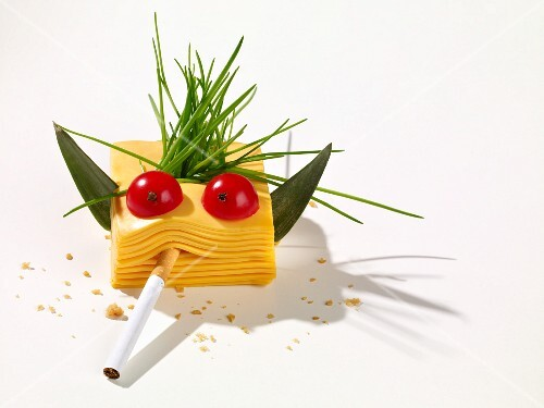 A cheese face made from a stack of processed cheese with a cigarette