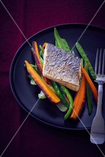 Branzini fillet on a bed of vegetables