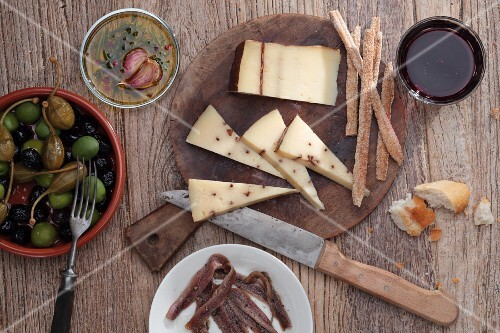 Spanish cheese with breadsticks, anchovies and olives