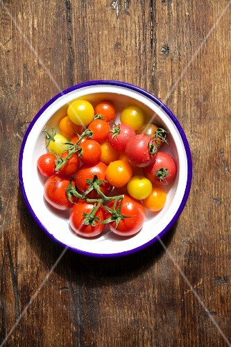 Various tomatoes in a bowl on a wooden table