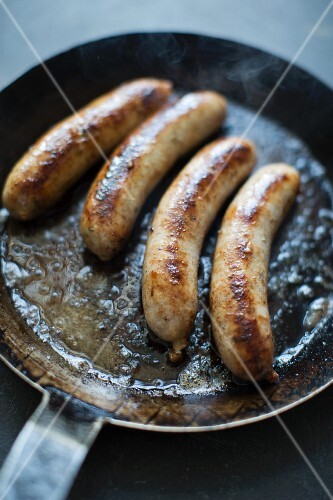 Four sausages in a pan