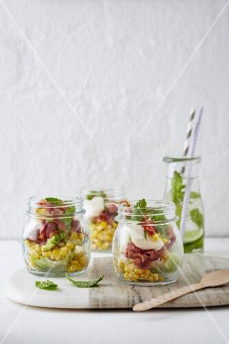 Sweet corn salad with bacon and aioli in jars