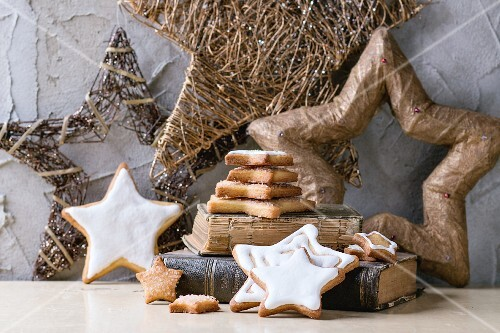 Iced, star-shaped Christmas cookies on old book with Christmas decorations