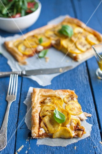 A puff pastry tart with yellow courgette, pesto rosso, cheese and basil