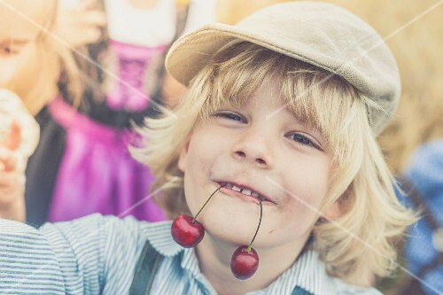 A blond boy holding two cherries in his mouth