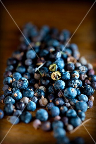 A close-up of wild Italian juniper berries on a wooden table