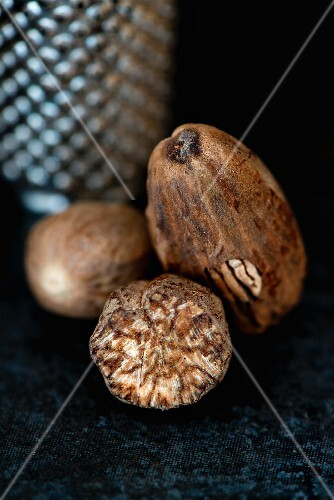 A close-up of whole and partially grated nutmegs