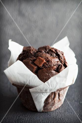 A chocolate fudge muffin in white paper