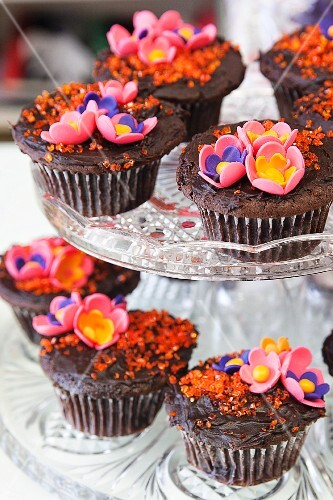 Choclate cupcakes with colourful sugar flowers on a cake stand