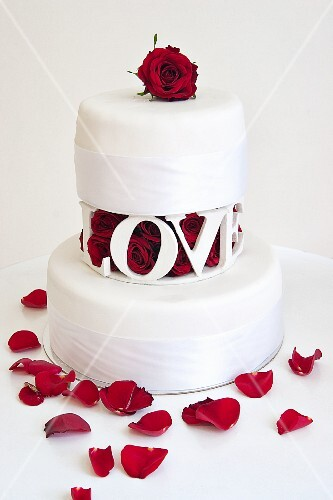 A two tier wedding cake with with red rose petals