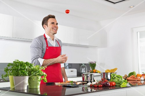 A man wearing an apron laughing and juggling tomatoes in a kitchen