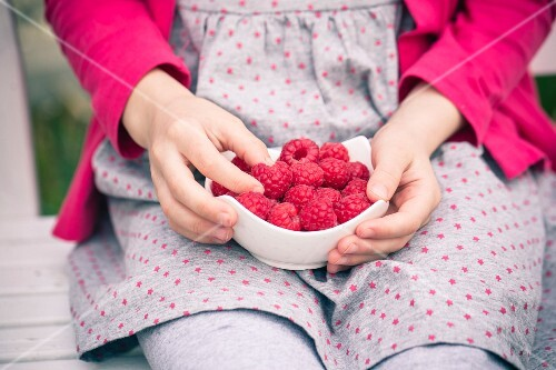 A little girl holding a bowl of fresh strawberries