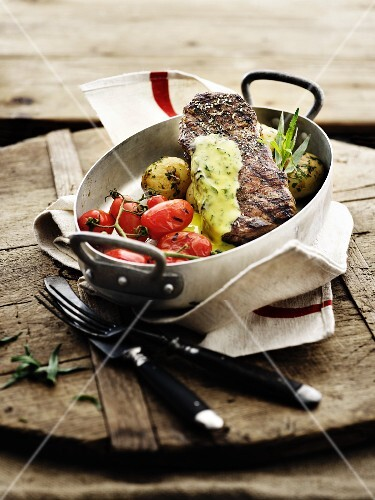 Beef steak with oven-roasted vegetables and herb sauce