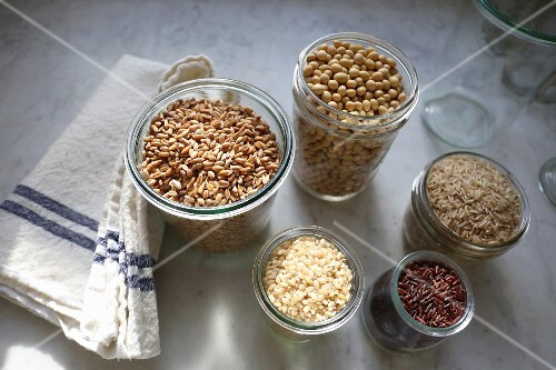 Organic spelt, soya beans, long grain rice, red Himalayan rice and short grain rice in jars on a marble surface