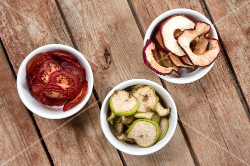 Dried tomatoes, pears and apples in white bowls on a wooden table