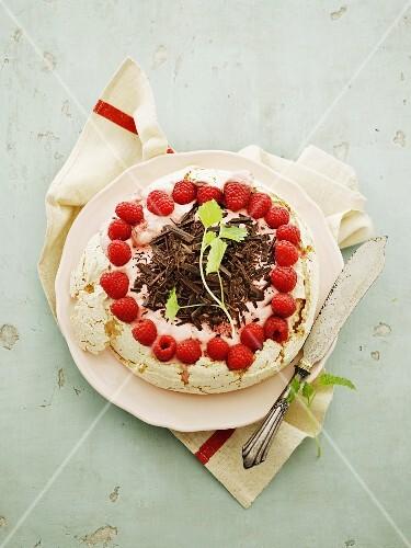 A meringue tart with raspberry cream and fresh raspberries