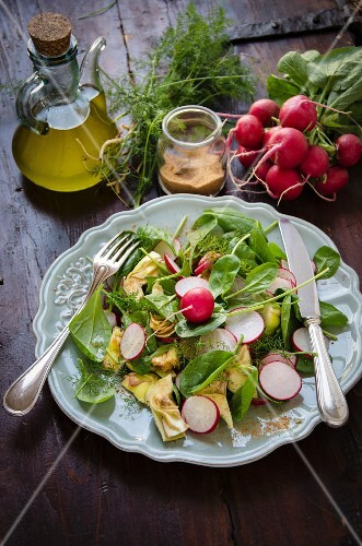 A mixed salad with baby spinach, radishes and artichokes