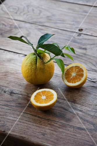 Organic oranges, whole and halved, with leaves