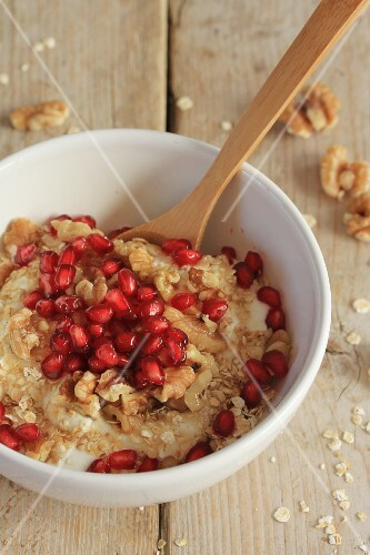 Vegan coconut yoghurt with oats, walnuts, pomegranate seeds and agave syrup