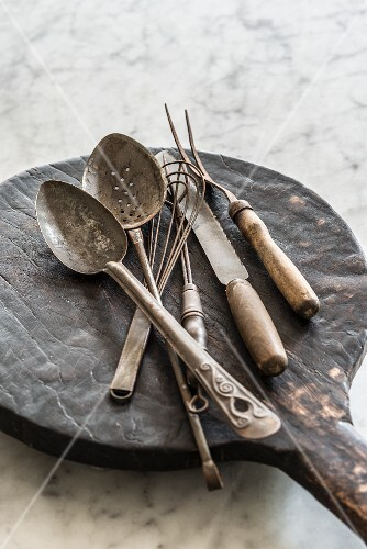 Various old cooking utensils on a wooden board