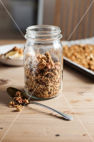 Granola in a storage jar and on a baking tray in the background