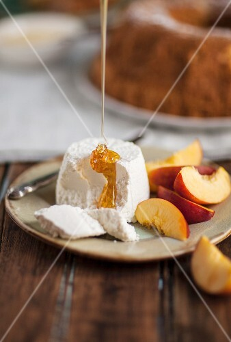 Honey being drizzled onto goats cheese with nectarine wedges next to it