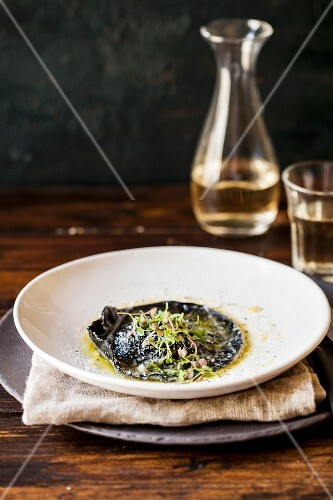 A giant black ravioli in brown butter with cress