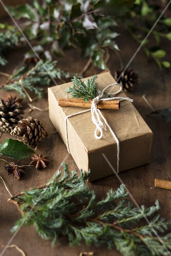 A gift decorated with conifer sprigs and cinnamon sticks